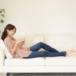 ソファでタブレットを見ながらくつろぐ女性
