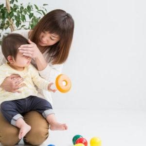 子供の熱があるかを確認している女性